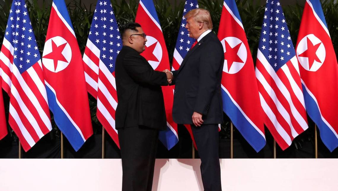 U.S. President Donald Trump and North Korea's leader Kim Jong Un shake hands during a summit at the Capella Hotel on the resort island of Sentosa, Singapore